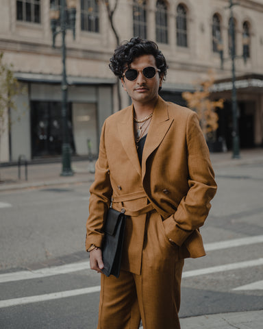 Ayaz Raja is standing outside, wearing a brown strappy suit and adesso man sunglasses