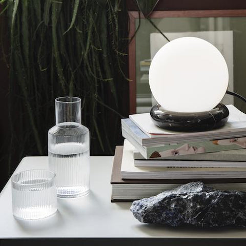 The Ripple Carafe Set from Ferm Living next to a lamp and stack of magazines