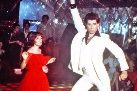 John Travolta in Saturday Night fever wearing a white suit and dancing with a woman in a red dress