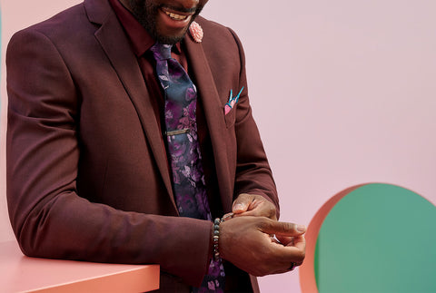 a man in a burgundy suit, with a floral pattern tie, adjusts his bracelet