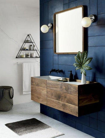 A sustainable bathroom with a wooden vanity and gold mirror