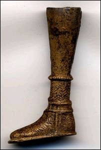 A bronze razor handle depicting a foot and sock