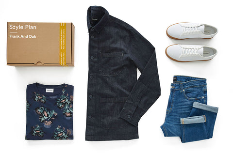 A flat lay of a men's t-shirt, jacket, blue jeans, and white sneakers from Frank and Oak's style plan subscription