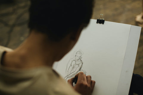 A man is drawing a figure of a person