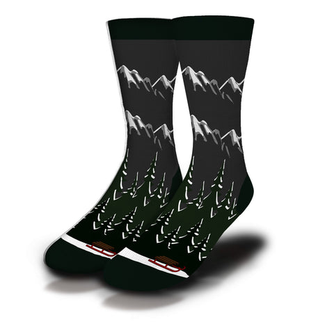 A rendering of a pair of socks from the Classroom Champions collection featuring a snowy mountain backdrop with a red sled