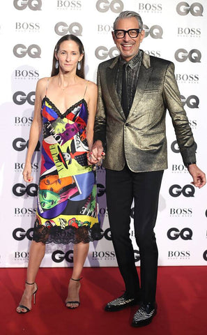 Jeff Goldblum and his fiancée at an award show. He is wearing black trousers and a gold blazer. She is wearing a bright, printed dress with lace trim and heels