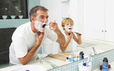 Dad teaching son how to shave his face