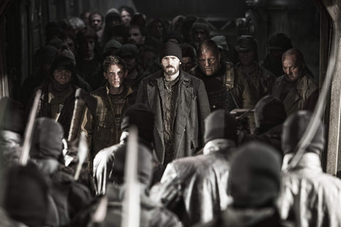 Chris Evans in Snowpiercer - he is walking in a large group of people, in what seems to be a standoff with an enemy group