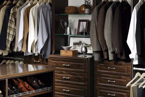 A well organized men's closet with dress shirts and blazers neatly pressed and hung