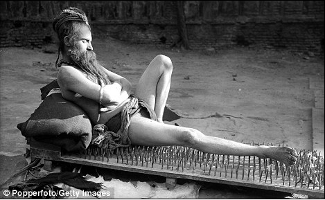 Indian man laying on an ancient bed of nails