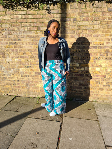 Lena King Black woman standing in front of a brick wall wearing a pair of teal and grey trousers, a denim jacket and white trainers.  She has her hands in her pocket and is wearing a pair of blue earrings.