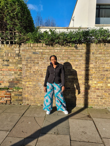 Lena King Black woman standing in front of a brick wall wearing a pair of teal and grey trousers, a black suit jacket and white trainers.  She has her hands at her sides and is wearing a pair of blue earrings.
