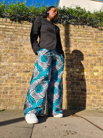Lena King Black woman standing in front of a brick wall wearing a pair of teal and grey trousers, a black suit jacket and white trainers.  She has her hands in her pocket and is wearing a pair of blue earrings.