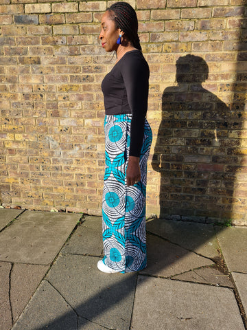 Lena King Black woman standing in front of a brick wall wearing a pair of teal and grey trousers, a black top and white trainers.  She is standing with her left shoulder facing the camera. She is at right angles to the wall and facing in that direction.  She has her hands at her side and is wearing a pair of blue earrings.