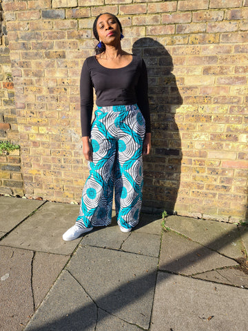 Lena King Black woman standing in front of a brick wall wearing a pair of teal and grey trousers, a black top and white trainers.  She has her hands at her sides and is wearing a pair of blue earrings.