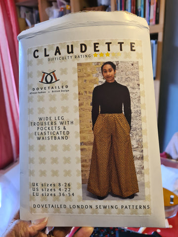 Black woman's hand holding an opened sewing pattern. The sewing pattern has the name Claudette on the front and features a dual heritage female wearing a pair of trousers.