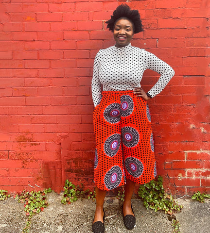 Black woman standing in front of a red brick wall wearing a pair of culottes made in African wax print fabric in red fabric with large circular motifs and a white top.
