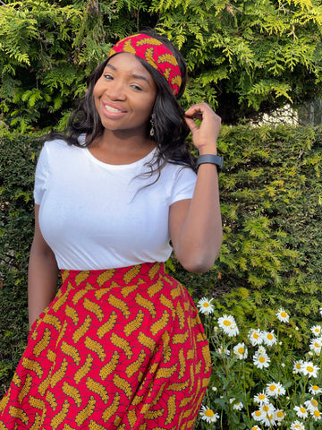 Ruth is a black woman with long straight black hair. She is wearing a white top with a red African wax print circle skirt and a matching headband.