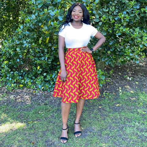Ruth is a black woman with long straight black hair. She is wearing a white top with a red African wax print circle skirt and black strappy shoes.