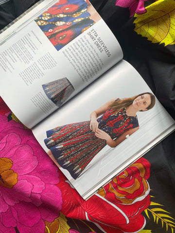 Sewing book lying open at the Etta shirt dress pattern lying on a piece of black with pink red and yellow African wax print fabric.