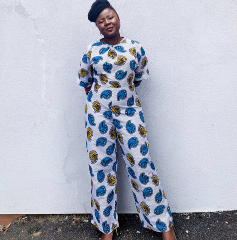 Ruth is a black woman with afro hair styled into a quiff at the front. She is wearing the Jennifer jumpsuit in Sea Shells on White African wax print fabric.  The fabric has mustard and blue sea shells on a white background with black polka dots.