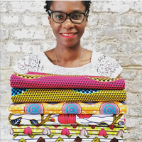 Adaku Parker Black woman smiling owner of Dovetailed African wax print fabrics. Wearing white top, red lipstick and black glasses. She is holding a bundle of 6 folded African wax print fabric bundles in her arms.