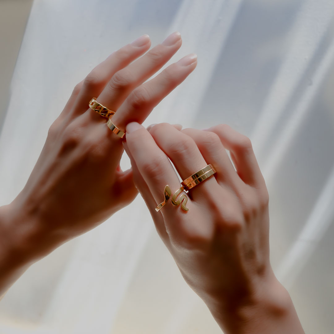 Hands wearing chain band serpent meridian rings gold