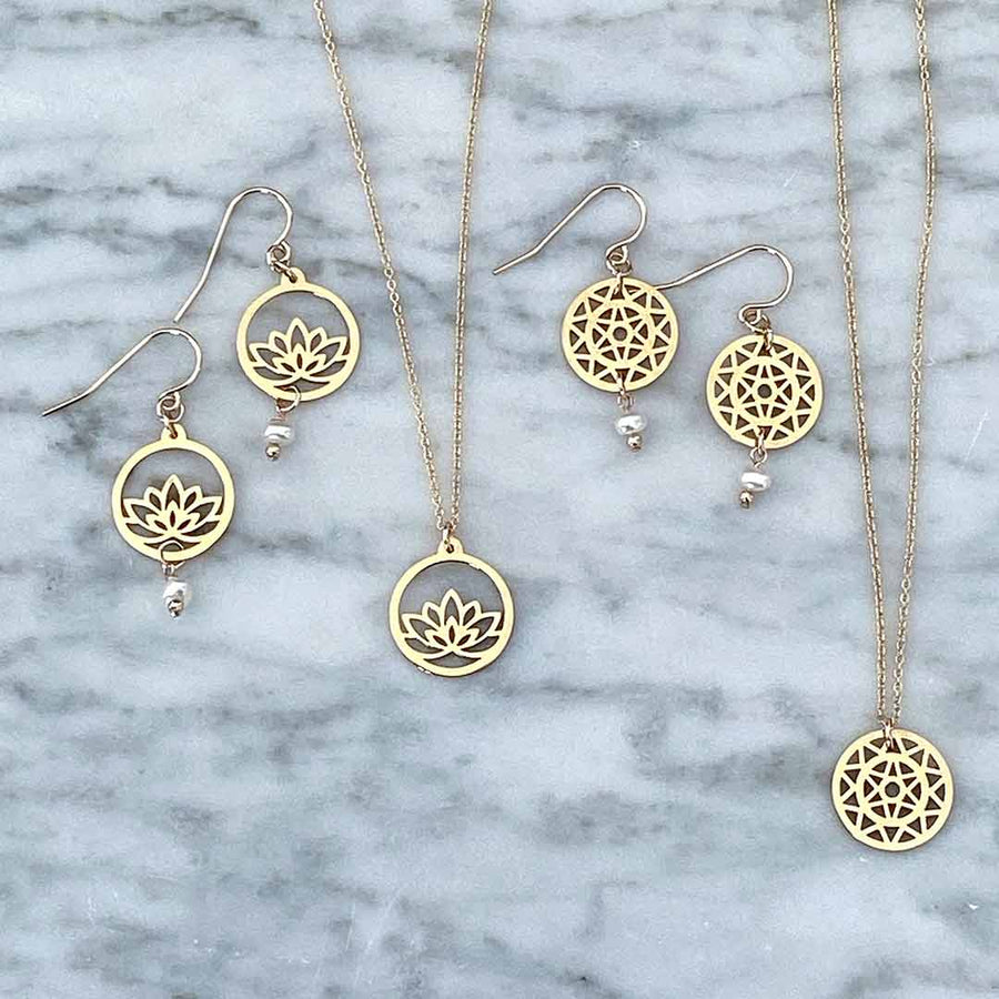 Lotus and Dandelion hook earrings and necklace flatlay gold