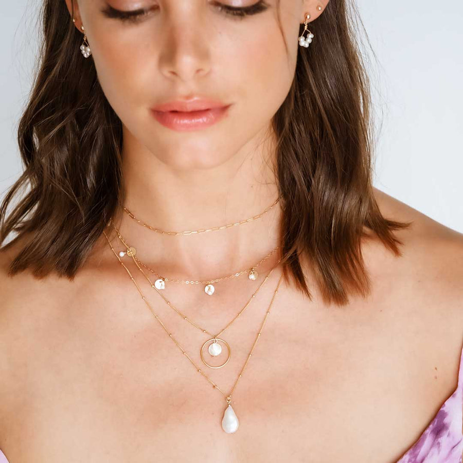 Model-wearing-Angel-5-earrings,-charmed-phoebe-and-halo-moonglow-necklaces-gold-and-pearl-lighter