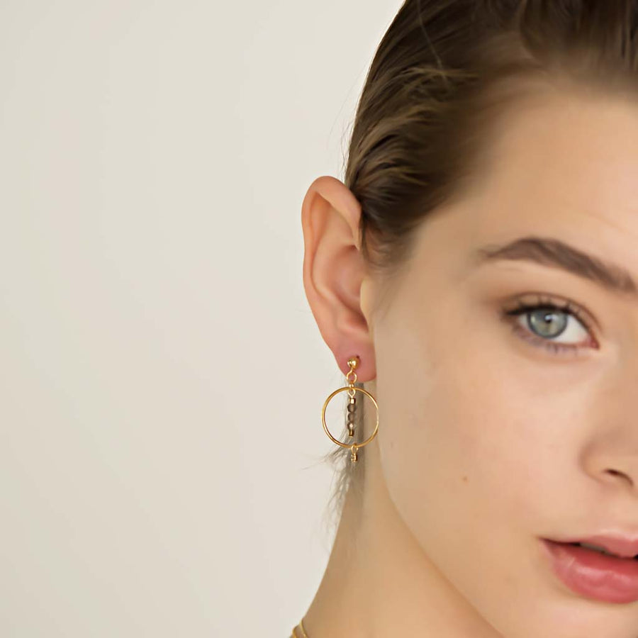 Model wearing Halo Equilibria Earrings - Gold and Smoky Quartz