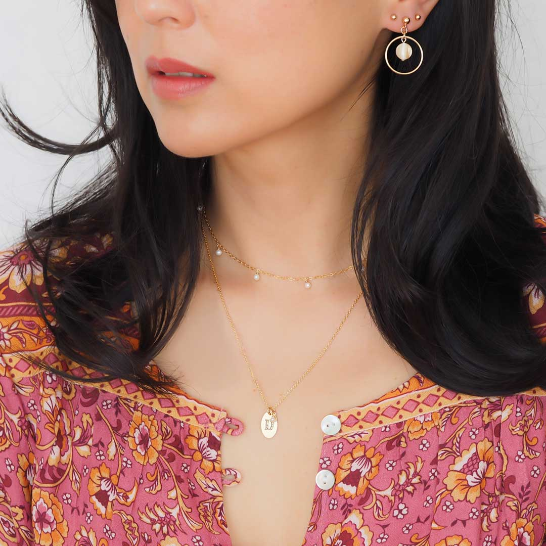 Model wearing Halo Moonglow earrings, charmed and loveletter necklaces