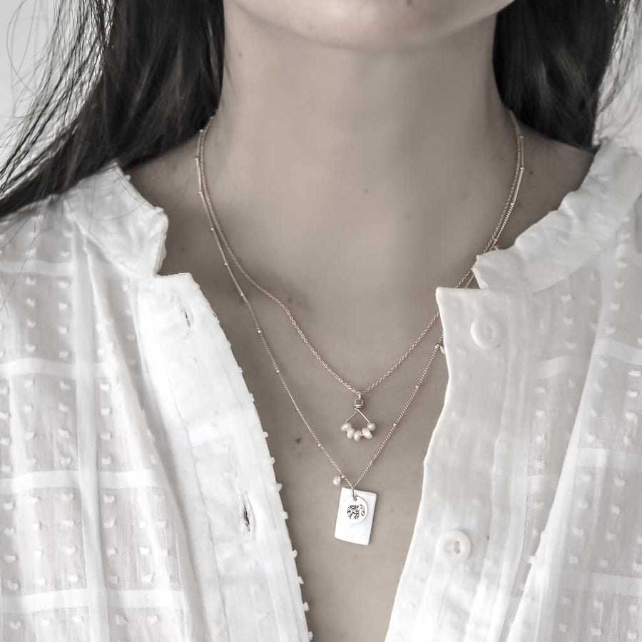 Model wearing Angle 5 and Enchanted Elephant necklaces gold and Pearl