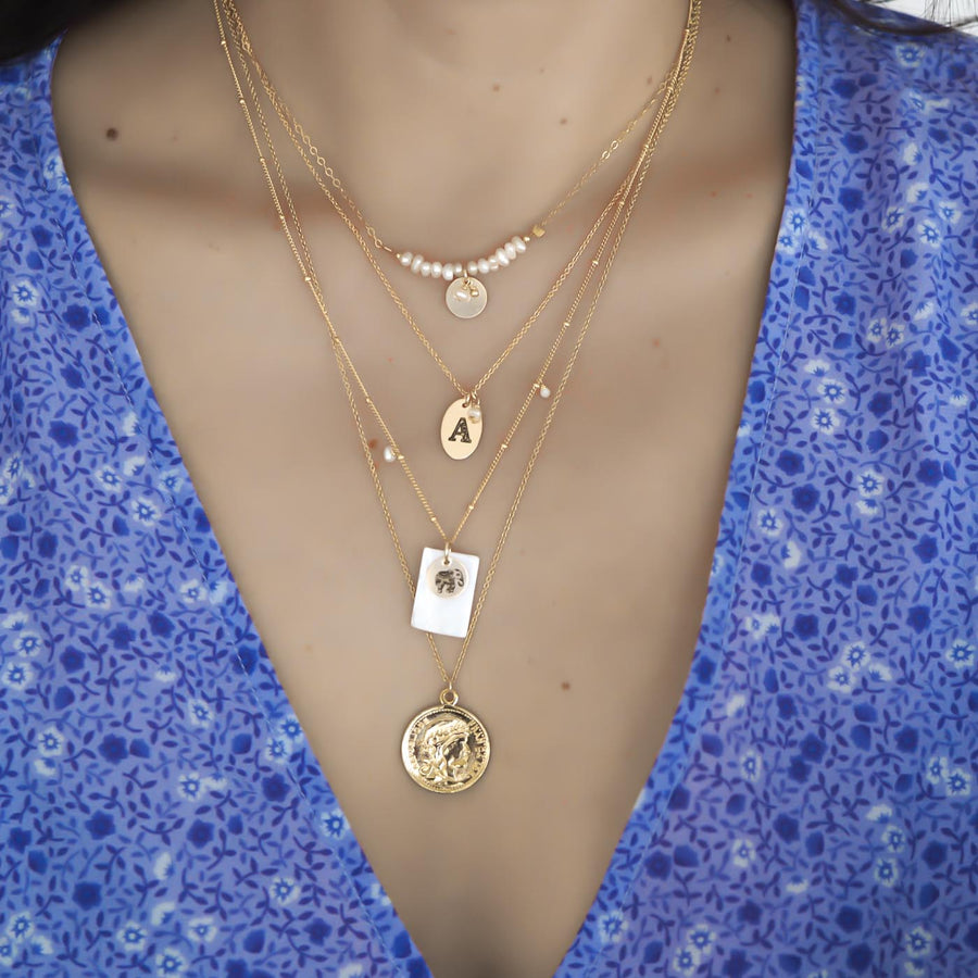 Model wearing Aura, love letter, enchanted elephant and coin necklaces