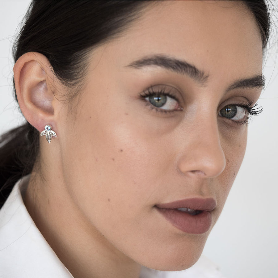 Model wearing Bloom earrings silver swiss blue topaz