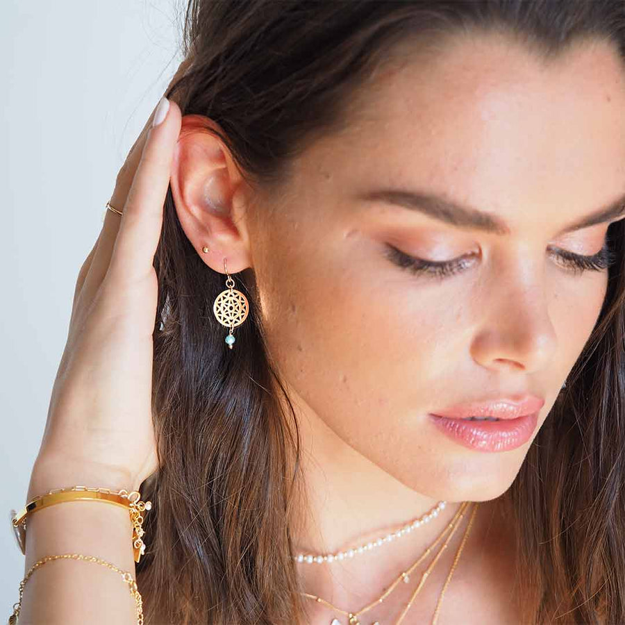 Model wearing Dandelion Hook earrings gold and amazonite