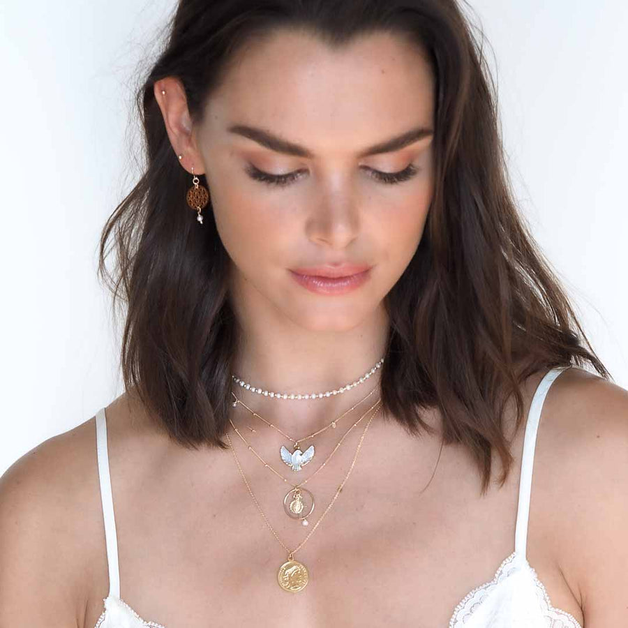 Model wearing Dove,Halo faith, heirloom gold coin necklaces,Dandelion earring gold and pearl