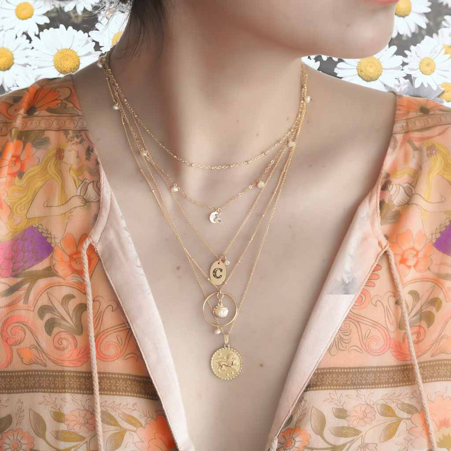 Model wearing Satellite chain, Charmed, Love Letter, Halo Seashore and Gold Leo necklaces Gold and Pearl