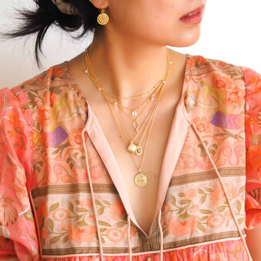 Model wearing Satellite chain, Charmed,Orbit,  Love Letter, Seashell and Gold Leo necklaces Gold and Pearl