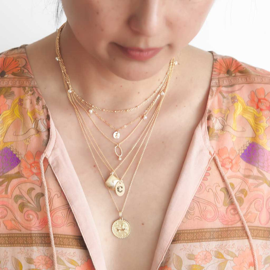 Model wearing Satellite chain, charmed,orbit,  seashell, Love letter, Gold Leo necklaces in gold and pearl smoother-2