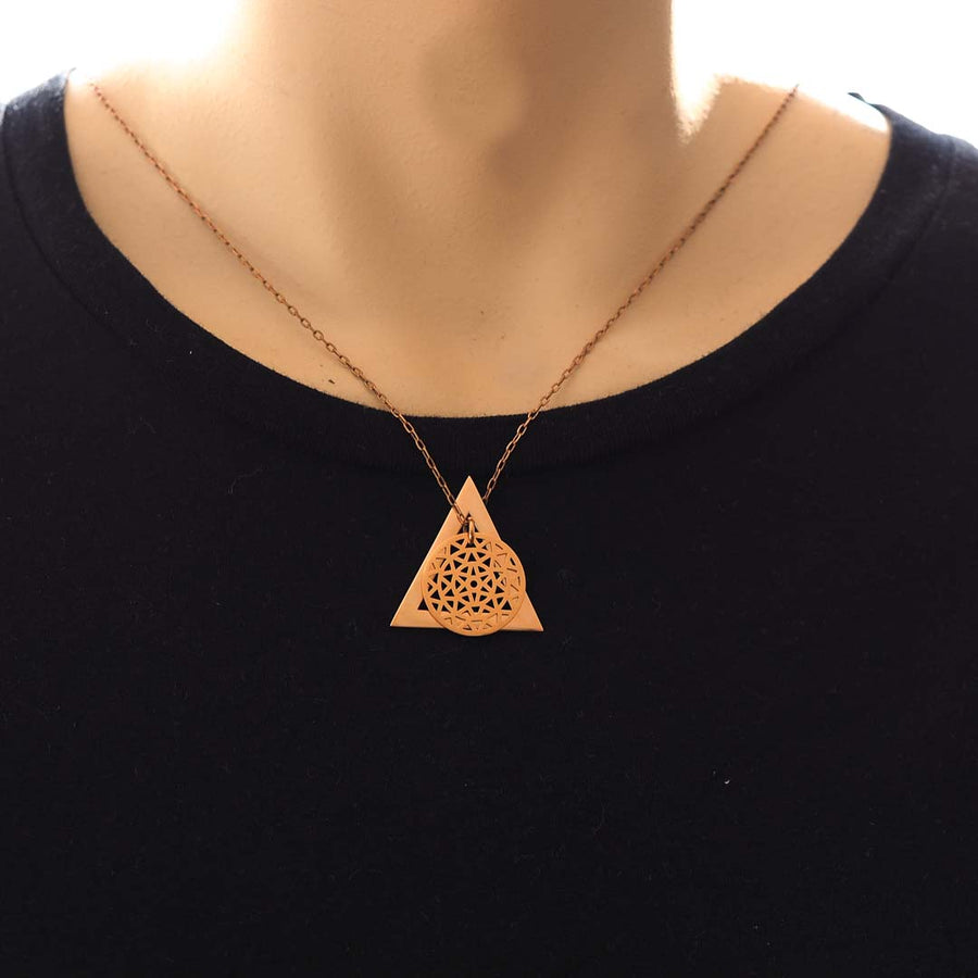 Model wearing dandelion and delta glyph pendant rose gold short chain