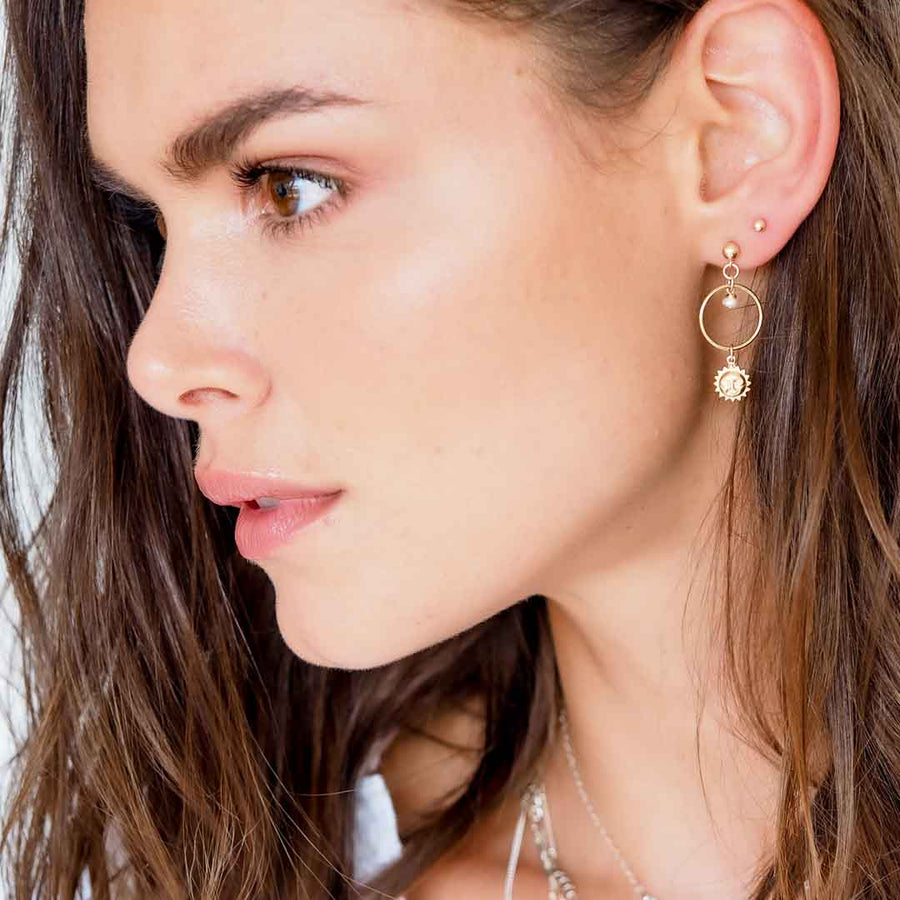 Model wearing Halo Sun earrings gold and pearl