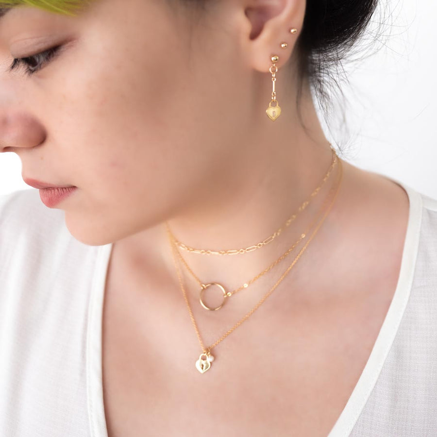 Model wearing Love locket ring chain mail necklaces layered gold