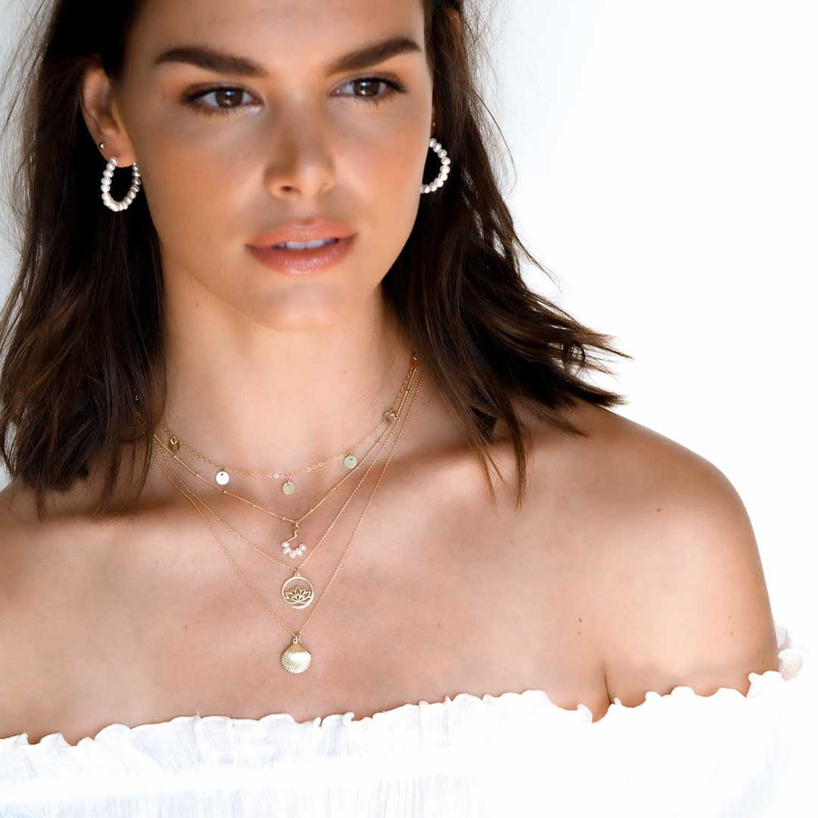 Model wearing Pearl earrings, Charmed,angel 5, lotus, impressions seashore necklaces gold and pearl layered