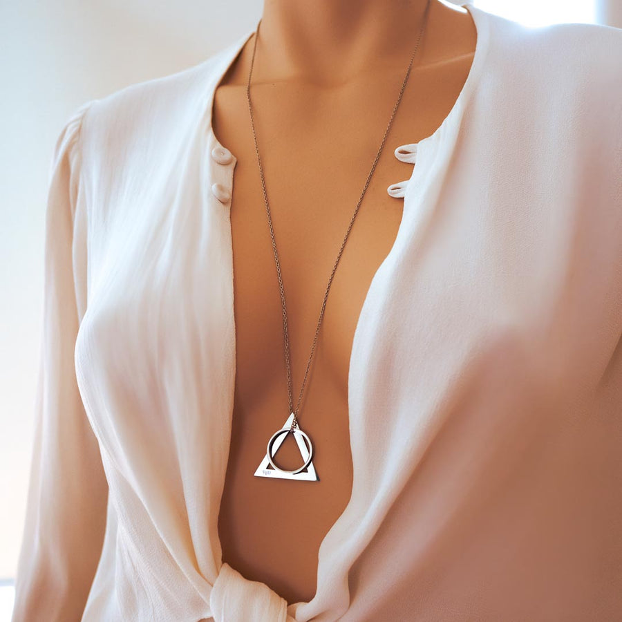 model wearing deltaglyph rof pendant rhodium long chain