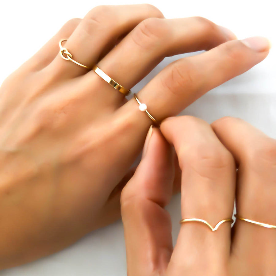 Hand model wearing Knot, band, baby pearl, wishbone rings