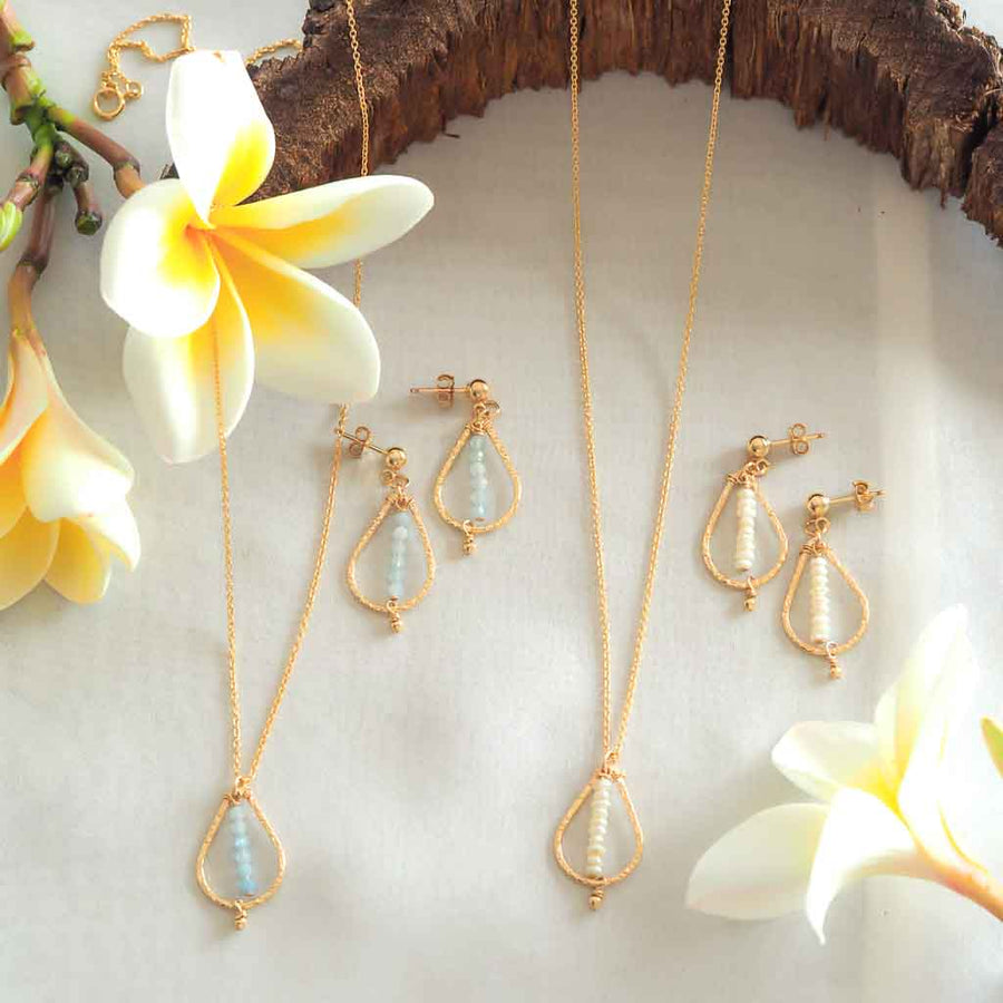Candle Flame Earrings and Necklaces Gold Pearl and Aquamarine flatlay