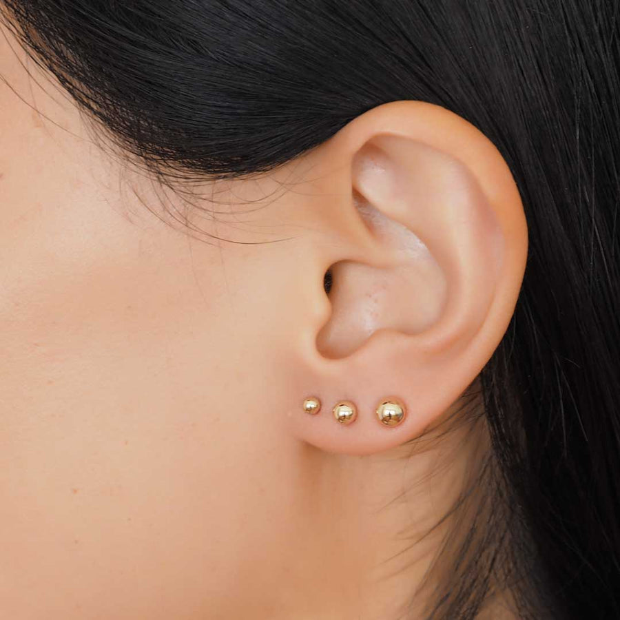 Model wearing 3 perfect dot earrings closeup