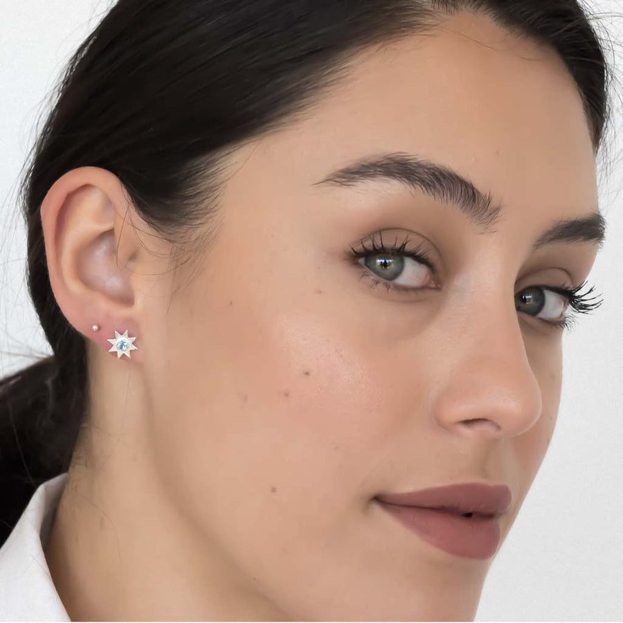 model wearing solstice star earrings silver swiss blue topaz