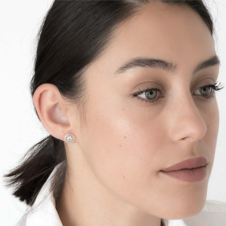 model wearing taraxacum earrings silver swiss blue topaz