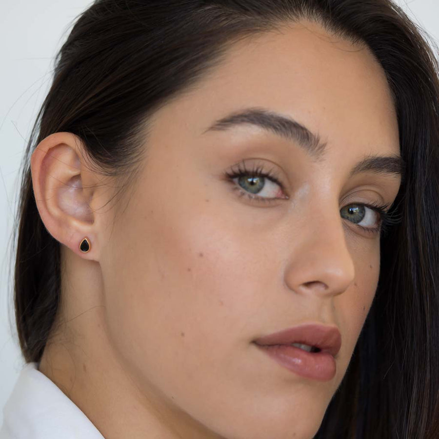 model wearing teardrop stud earrings rose gold black spinel